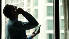 Silhouette of successful businessman gets great news on smartphone  HD - stock footage