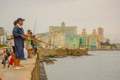 Stock Photo of HAVANA, CUBA - AUGUST 30, 2015: Local men fish on the sea in Havana