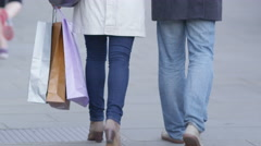 4K Couple with shopping bags walk away from camera through city street - stock footage