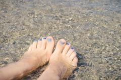 Woman feet with blue pedicure relaxing in water on the seashore Stock Photos