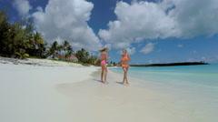 Young Caucasian female sisters in swimwear on luxury island beach - stock footage