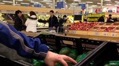 Man selecting avocado in grocery store Stock Footage