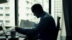 Businessman reading and analyzing documents sitting in the office Stock Footage