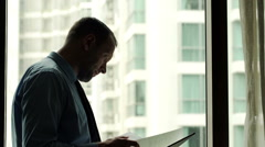 Businessman reading and analyzing documents by the window in the office Stock Footage