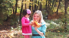 Mother and daughter walking in the park autumn Stock Footage