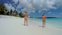 Young Caucasian female sisters in swimwear on island beach - stock footage