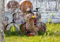 Paintball sportsman in ambush behind rusty barrels - stock photo