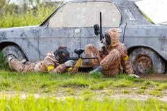 Stock Photo of Two friends defend old car in paintball mission