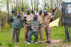 Team of five men with flag play paintball - stock photo