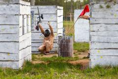 Extreme capture of red flag in paintball game - stock photo
