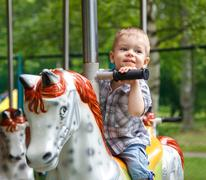 Smiling child riding a toy horse carousel - stock photo