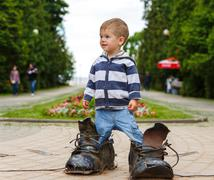 Puzzled two years old boy standing in giant boots Stock Photos