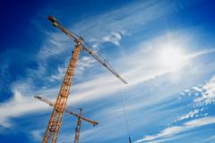 Two Industrial Cranes Working on Construction Site Stock Photos