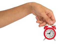 Humans hand holding alarm clock on white Stock Photos