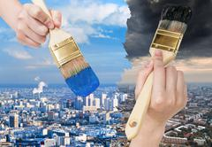 Paintbrush paints blue clean and dark dirty city Stock Photos
