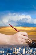 Paintbrush paints smog sky over blue city Stock Photos