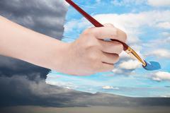Paintbrush paints blue sky on storm clouds Stock Photos