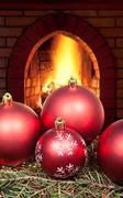 red Christmas balls on spruce tree and fireplace - stock photo