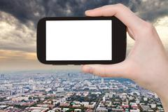Smartphone and storm clouds over city Stock Photos
