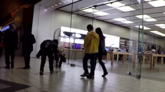 People helping woman picking up her money in front of apple store Stock Footage