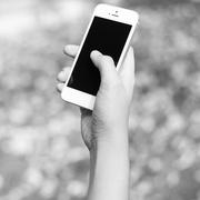 Woman hand holding smartphone against on background black and white color Stock Photos
