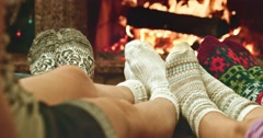 Feet in woolen socks warming by cozy fire. Family with two kids near fireplace. - stock footage