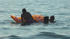 Bikini teen friends having fun on Air Bed at sea sunset Stock Footage