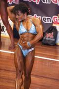Female bodybuilder in abdominals and thighs pose and blue bikini - stock photo