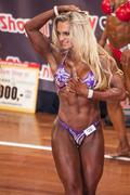 Female bodybuilder in abdominals and thighs pose on stage Stock Photos