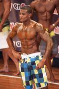 Male fitness contestant shows his best physique on stage - stock photo