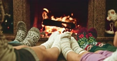Feet in woolen socks warming by cozy fire. Family with two kids near fireplace. Stock Footage