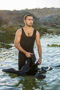 A young surfer putting on his wetsuit on the beach. man in a suit underwater hun Stock Photos