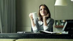 Young businesswoman finishing her work on laptop and drinking coffee at office Stock Footage