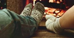 Feet in woolen socks warming by cozy fire. Family couple near the fireplace. - stock footage