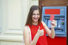Young woman withdrawing money from credit card at ATM Stock Photos