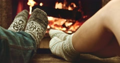 Feet in woolen socks warming by cozy fire. Family couple near the fireplace. Stock Footage