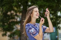 Young beautiful brunette tints shine your lips with a brush - stock photo