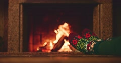 Woman relaxes by warm fire and wriggles toes. Cozy evening by fireplace at home. Stock Footage