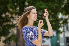 Young beautiful brunette tints shine your lips with a brush Stock Photos