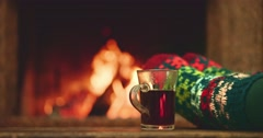 Woman relaxes by warm fire with a cup of tea and wriggles toes in woollen socks. Stock Footage
