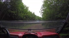 Low shot of a large four wheeler riding through grass and trees Stock Footage