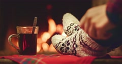 Woman relaxes by warm fire in woollen socks and stirs hot drink with teaspoon. Stock Footage