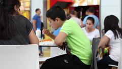City Family dining in a large food court mall Stock Footage