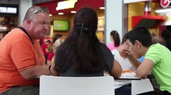 City fat father, mother and son in a restaurant eating high-calorie foods Stock Footage
