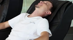 City Man first sat in a massage chair and share new sensations Stock Footage