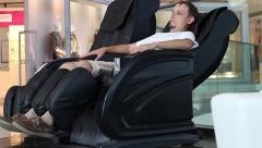 City Man relaxes in a paid massage chair Stock Footage