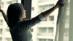 Businesswoman unveil curtains and stretching her arms by the window Stock Footage