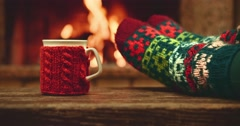 Woman relaxes by warm fire with cup of hot drink, wriggles toes in woollen socks Stock Footage