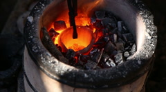 Blacksmith tongs pulls a red-hot crucible with the metal from the hearth Stock Footage