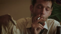 Young depressed clerk smokes cigarette and nervously grabs his head - stock footage